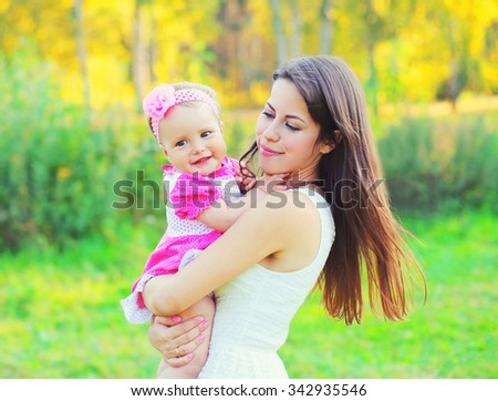Happy young mother and baby on hands in summer day - stock photo
