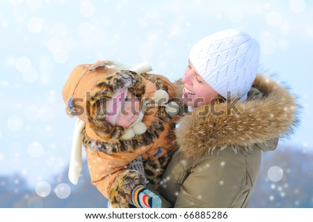 Happy young mother and daughter in winter clothing to have fun - stock photo