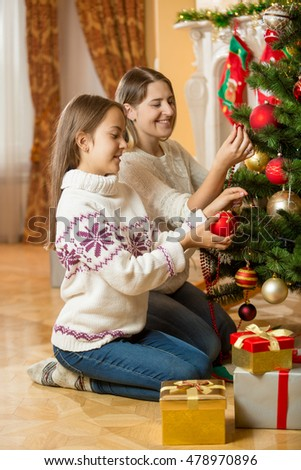 Happy young mother and daughter sitting on floor at living room and decorating Christmas tree