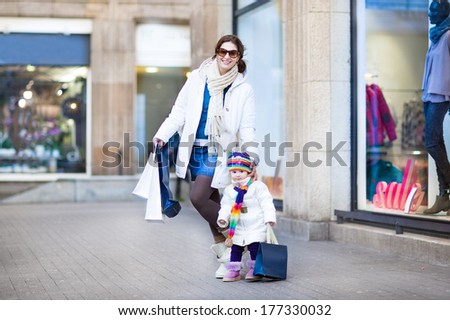 Happy young mother and her cute toddler daughter enjoying shopping in a city mall during winter sale - stock photo