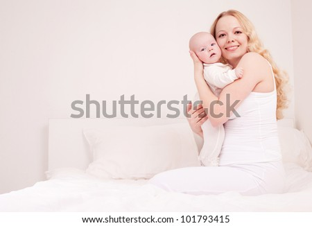 happy young mother and her four months old daughter in bed at home