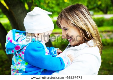 happy young mother and her little son spending time outdoor in the park - stock photo