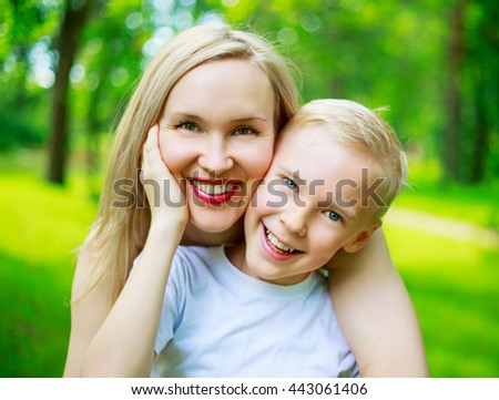 happy young mother and her nine year old son in the summer park - stock photo