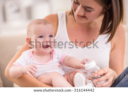 Happy young mother and her smiling baby. - stock photo