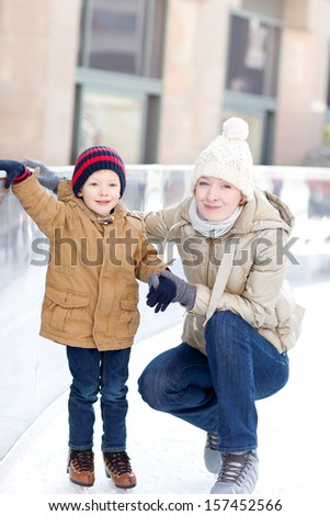 happy young mother and her smiling son ice skating at winter - stock photo