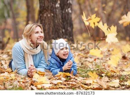 happy young mother and her son spending time in the autumn park - stock photo