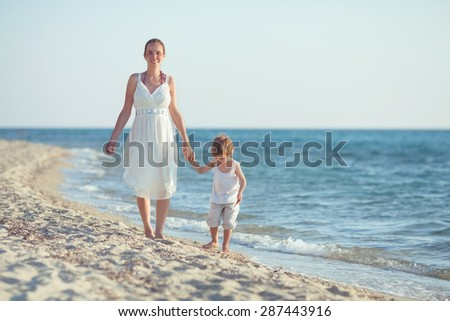Happy young mother and her son walking by the sea - stock photo