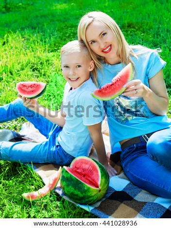 happy young mother and her ten year old son eating watermelon in the summer park
