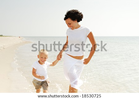 Happy young mother and male child holding hands and walking on beach. - stock photo