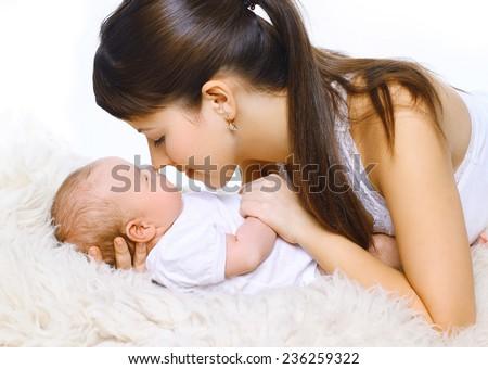 Happy young mother and sleepy baby - stock photo