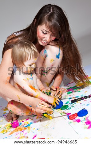happy young mother and son painting