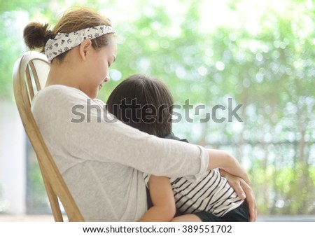 Happy young mother breastfeeding her son - stock photo