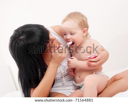 happy young mother feeding her baby with yogurt - stock photo