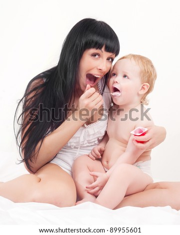happy young mother feeding her baby with yogurt  at home - stock photo
