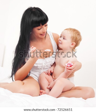 happy young mother feeding her baby with yogurt (focus on the baby) - stock photo