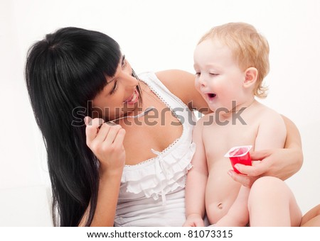 happy young mother feeding her baby with yogurt (focus on the mother) - stock photo