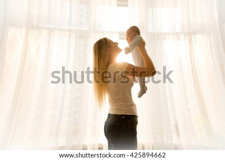 Happy young mother holding her baby at window at bright sunny day - stock photo