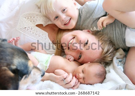 Happy Young Mother Laying in Bed with Toddler Son and Newborn Baby Daughter - stock photo