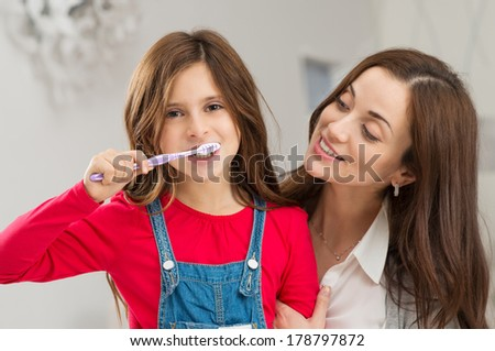 Happy Young Mother Looking At Her Daughter Brushing Teeth - stock photo