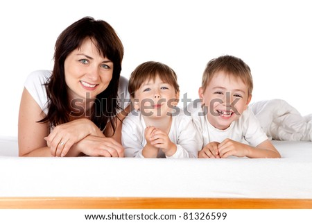 Happy young mother lying on bed with son and daughter; white background. - stock photo