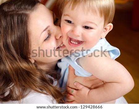 Happy young mother playing with cute son - stock photo