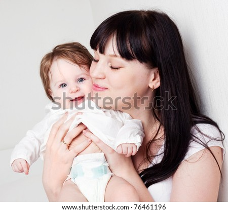 happy young mother playing with her baby on the bed at home