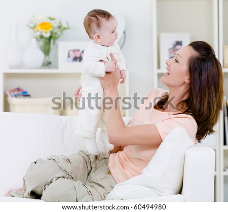 Happy young mother playing with her baby on the sofa - indoors - stock photo