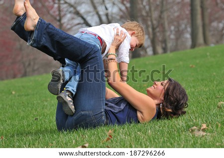happy young mother playing with her child in the park - stock photo
