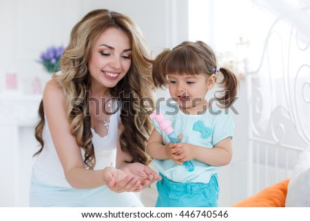 happy young mother playing with her daughter on the bed at home. Young mother hugging her daughter on the bed. daughter and mother are happy together - stock photo