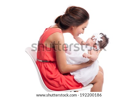 Happy young mother playing with her daughter. They're looking each other - stock photo
