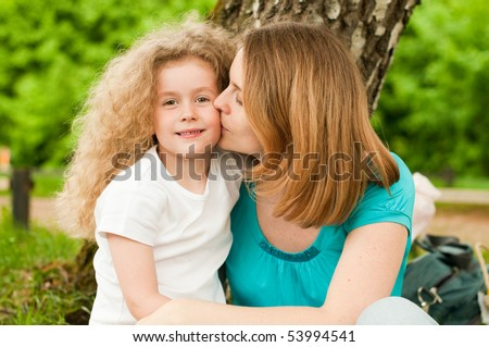 happy young mother sitting in park under tree and kissing her smiling small daughter - stock photo