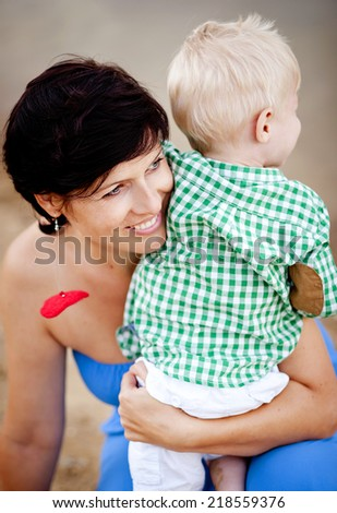 Happy young mother spending time together with her little son by the lake on the sandy beach - stock photo