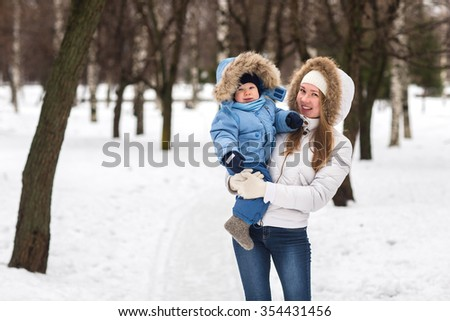 Happy young mother walking with her baby in the park in winter. Mother with her son in her arms.