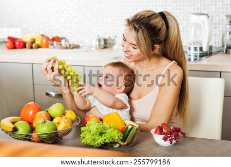 Happy young mother with a baby in the kitchen interior. Fresh vegetables and fruits.