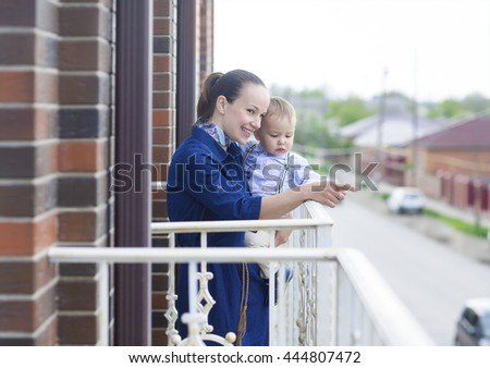 Happy young mother with baby boy on the balcony - stock photo