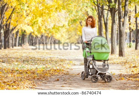 Happy young mother with baby in buggy walking in autumn park - stock photo