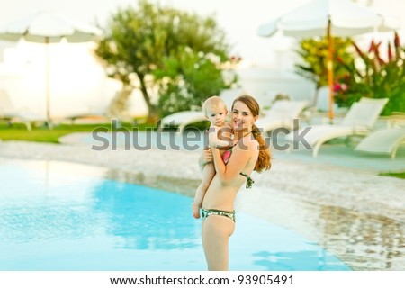 Happy young mother with cute baby standing in swimming pool - stock photo