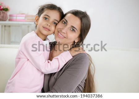 Happy young mother with daughter at home - stock photo