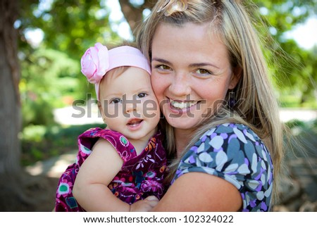 Happy young mother with her baby in park