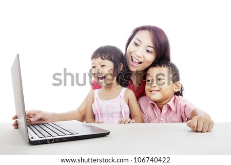 Happy young mother with her children using ultrabook laptop computer to enjoy entertainment - stock photo