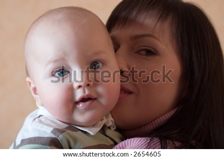 Happy young mother with her cute little son looking into the camera