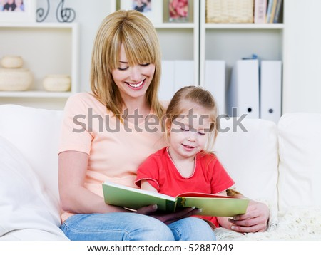 Happy young mother with her little smiling daughter reading the bood together - indoors - stock photo
