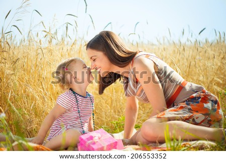 Happy young mother with little daughter having fun on wheat field in summer day  - stock photo