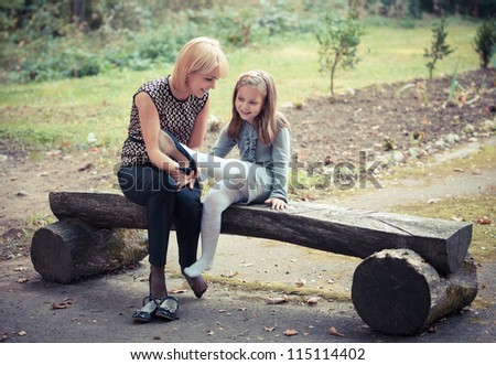 happy young mother with the daughter in park