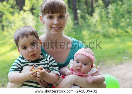 Happy young mother with two surprised kids in summer sunny forest  - stock photo
