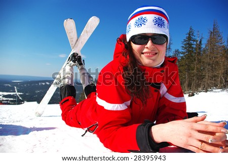 Happy young mountain skier resting on the slope - stock photo