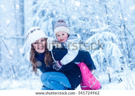Happy young mum and her little daughter in winter hats in snow forest at snowflakes background. outdoors winter leisure and lifestyle with kids. Beautiful family having fun during snowfall . - stock photo