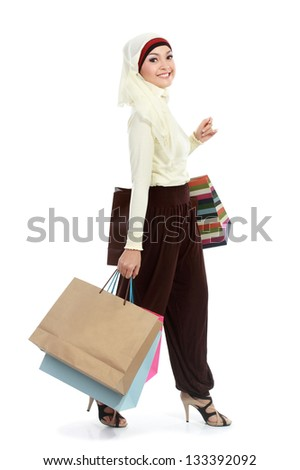 Happy young muslim woman with shopping bag isolated over white background - stock photo