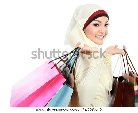 Happy young muslim woman with shopping bag isolated over white background