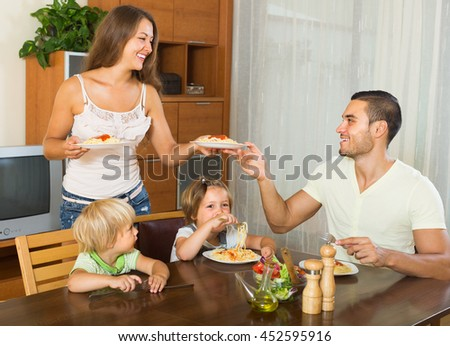 Happy young parents and two children having lunch with spaghetti at home together - stock photo